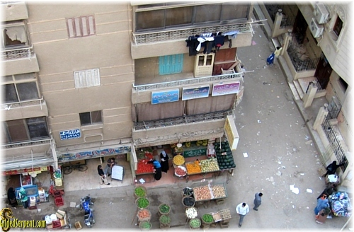In the photo is a typical street scene. Notice the wash hanging from the balcony over the green grocer's shop. To the right is the women's entrance to the neighborhood mosque. To the left is a meat store.