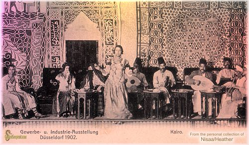 Postcard from 1902 showing dancers, singers, and musicians onstage at another typical sala (the postcard is from my personal collection)